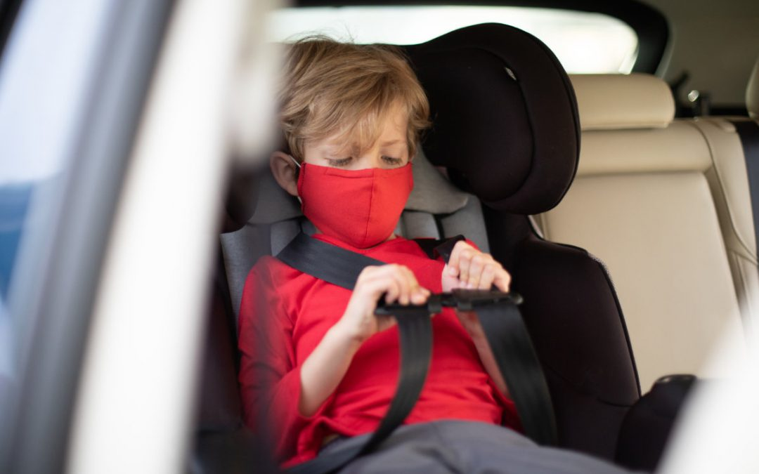 masked child in carseat